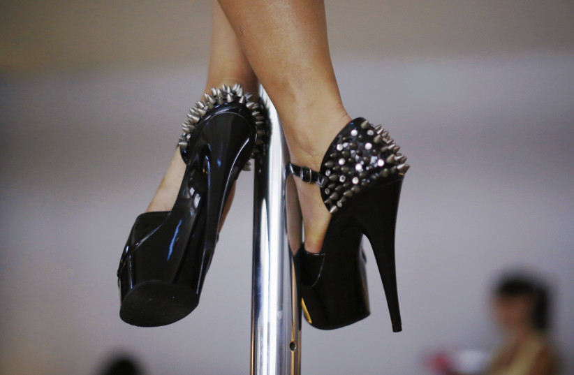 A woman wears spiked stilettos as she practises a pole dancing move during an International Women's Day event  (photo credit: JASON REED/REUTERS)