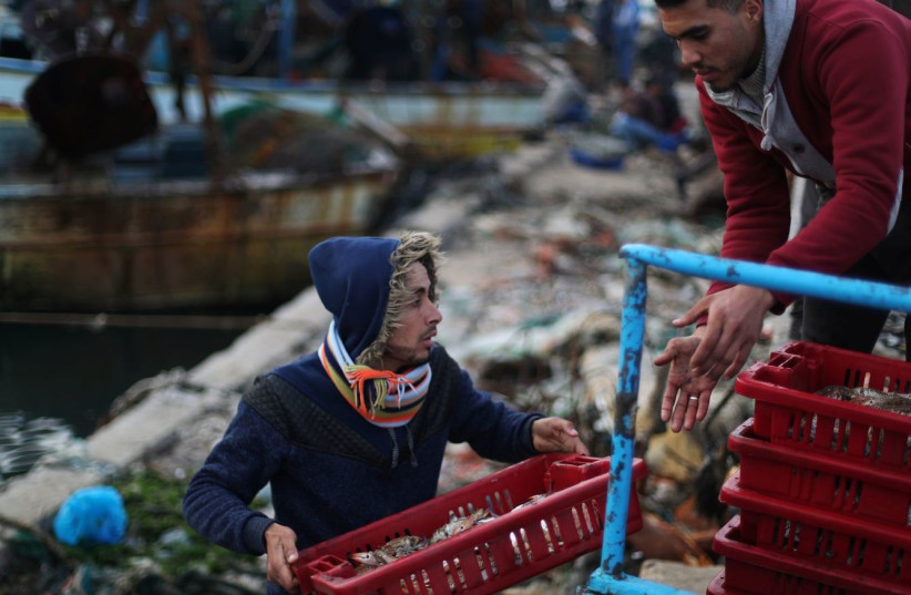 Fishermen unload their catch at the seaport of Gaza City, after Israel expanded fishing zone for Palestinians April 2, 2019. (photo credit: SUHAIB SALEM / REUTERS)
