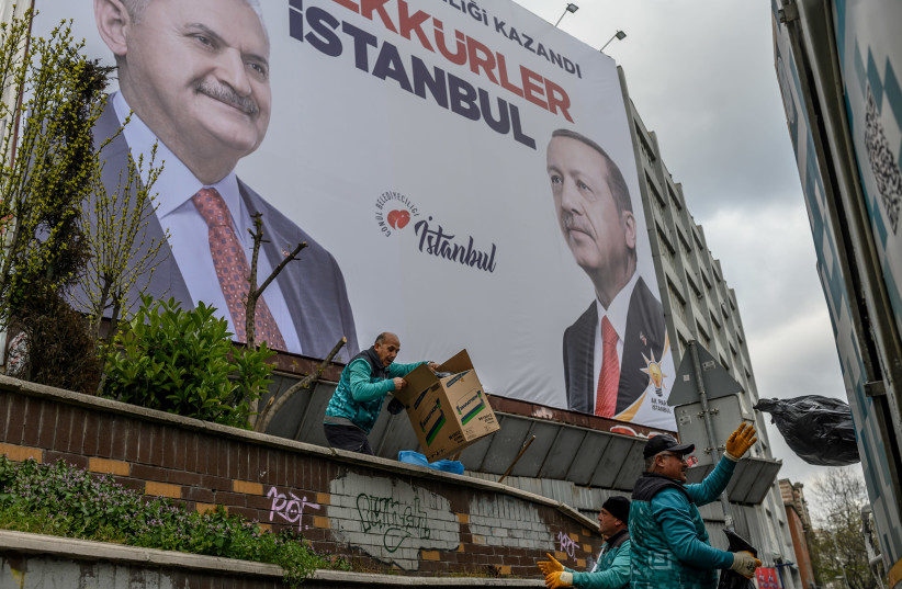 """Workers pick up the garbage next to a billboard reading """"Thank You Istanbul"""" and portraying AKP ruling party mayor candidate Binali Yildirim and President Recep Tayyip Erdogan, in Istanbul, on April 2, 2019 (photo credit: BULENT KILIC / AFP)"""