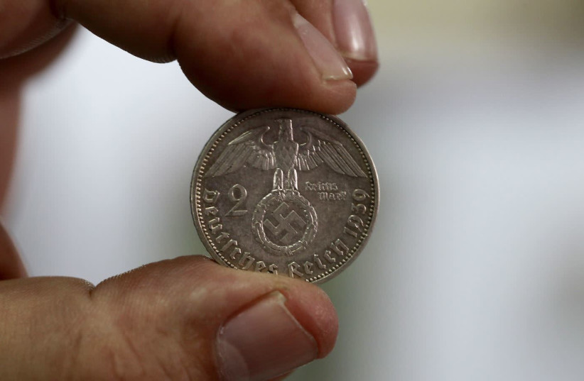 """Minor Blanco, owner of a shop called """"Caza de Tesoros"""" (Treasure Hunting), holds up a German coin from 1939 at his shop, in San Jose, Costa Rica September 23, 2015. The Los Angeles-based Simon Wiesenthal Center, which keeps tabs on anti-Semitism worldwide, sent Justice Minister Cecilia Sanchez Romer (photo credit: JUAN CARLOS ULATE / REUTERS)"""