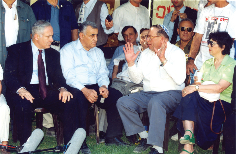 Prime Minister Benjamin Netanyahu and then-defense minister Yitzhak Mordechai listen to Yona Baumel (gesturing) as Baumel's wife, Miriam, (right) looks on, in 1997 (photo credit: BRIAN HENDLER)