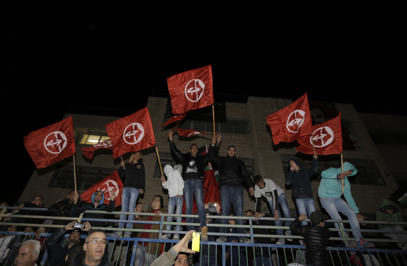 Palestinians hold Popular Front for the Liberation of Palestine (PFLP) flags, December 23, 2013 (photo credit: AMMAR AWAD / REUTERS)