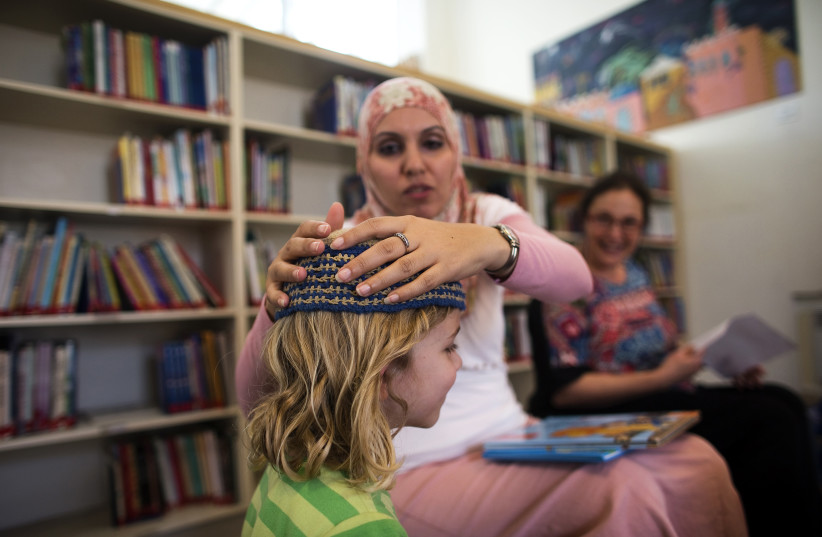 Alia Tunisi adjusts the skullcap of a student, Hand in Hand Arab Jewish bilingual school, Jerusalem, 2014. (photo credit: RONEN ZVULUN/REUTERS)