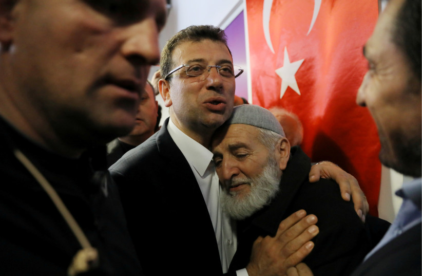 Ekrem Imamoglu, main opposition Republican People's Party (CHP) candidate for mayor of Istanbul, embraces his supporter at his election campaign office in Istanbul, Turkey April 1, 2019. (photo credit: HUSEYIN ALDEMIR/REUTERS)