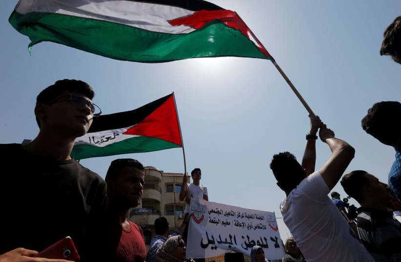 Palestinian refugees hold Palestinian flags and chant slogans during a protest in front of UNRWA office in Amman, September 2, 2018.  (photo credit: MUHAMMAD HAMED / REUTERS)