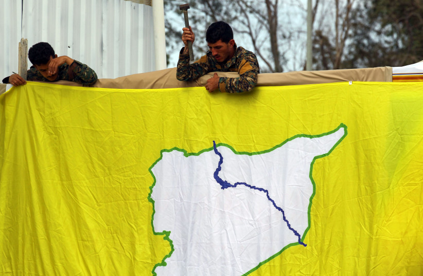 Fighters of Syrian Democratic Forces (SDF) put an SDF flag in al-Omar oil field in Deir Al Zor, Syria March 23, 2019 (photo credit: ABOUD HAMAM / REUTERS)