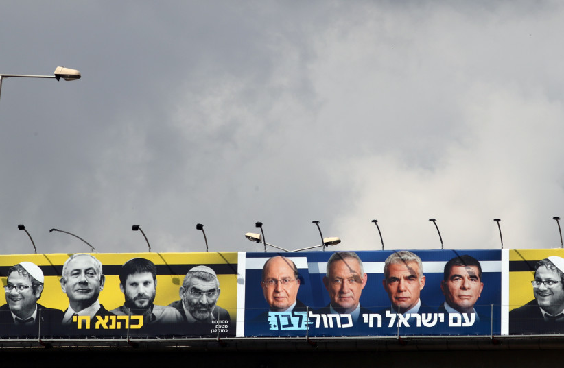 """A Blue and White campaign billboard that contrasted Prime Minister Benjamin Netanyahu and his far-Right allies with party leader Benny Gantz and his party members offering the caption """"The Nation of Israel Lives.""""  (photo credit: AMMAR AWAD / REUTERS)"""