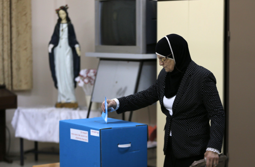 An Israeli Arab casts her ballot at a polling station inside a church in the northern town of Reineh, March 17, 2015. (photo credit: AMMAR AWAD / REUTERS)