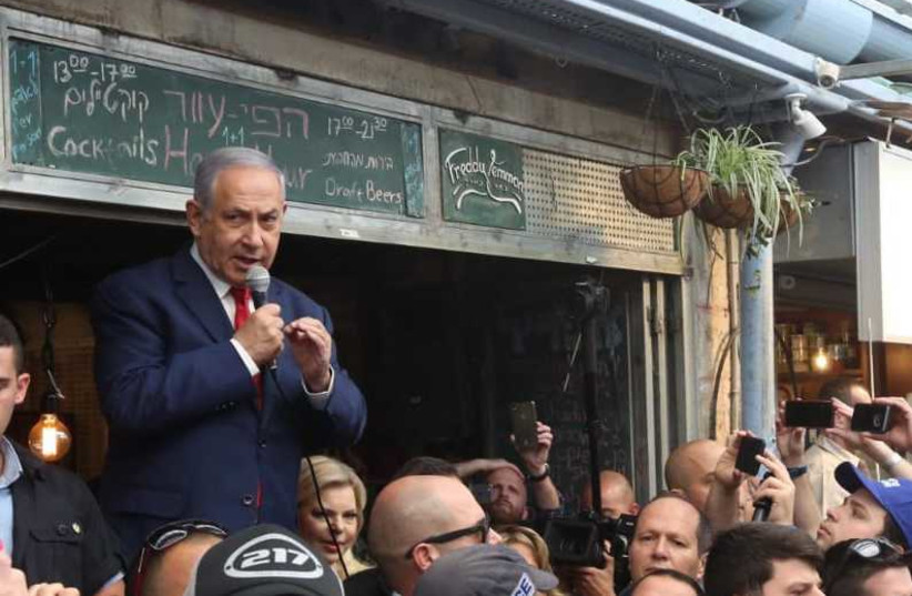 Prime Minister Benjamin Netanyahu surrounded by supporters at the Mahane Yehuda marketplace in Jerusalem April 8, 2019 (photo credit: MARC ISRAEL SELLEM)