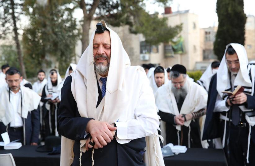 Shas leader Arye Deri prays at the grave of Rabbi Ovadia Yosef on the morning of elections (photo credit: YAAKOV COHEN/MAARIV)