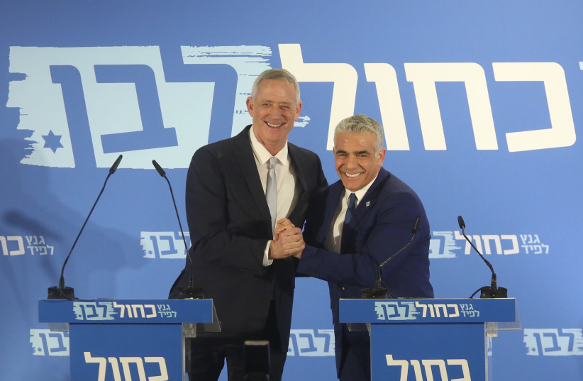 Blue and White leaders Benny Gantz (L) and Yair Lapid (R) embrace during a campaign event, February 21st, 2019 (photo credit: MARC ISRAEL SELLEM/THE JERUSALEM POST)