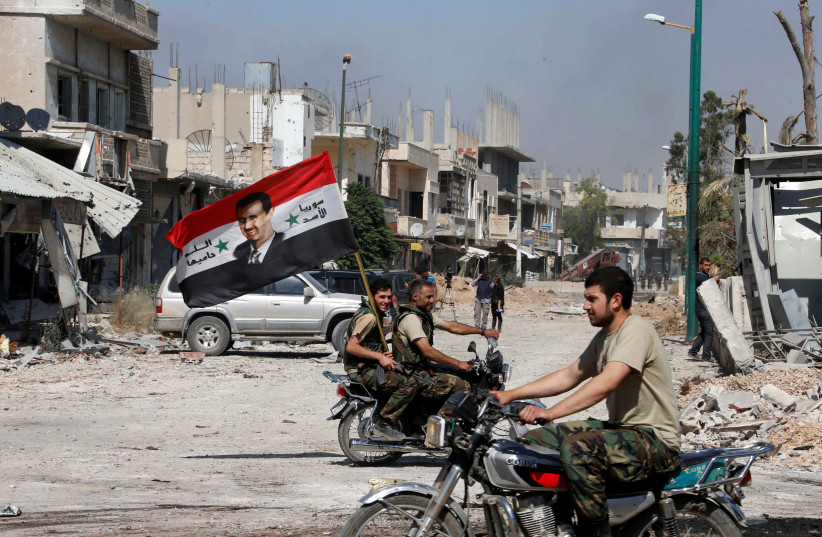 Forces loyal to Syria's President Bashar al-Assad carry the national flag as they ride on motorcycles in Qusair, Syria after the Syrian army took control from rebel fighters, June 5, 2013 (photo credit: REUTERS/MOHAMED AZAKIR)