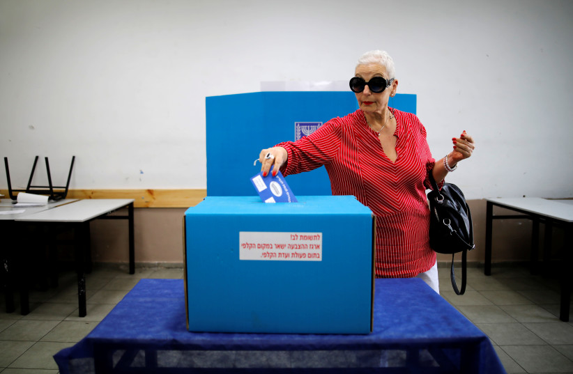 A woman casts her ballot as Israelis vote in a parliamentary election, at a polling station in Tel Aviv, Israel April 9, 2019 (photo credit: CORINNA KERN/REUTERS)