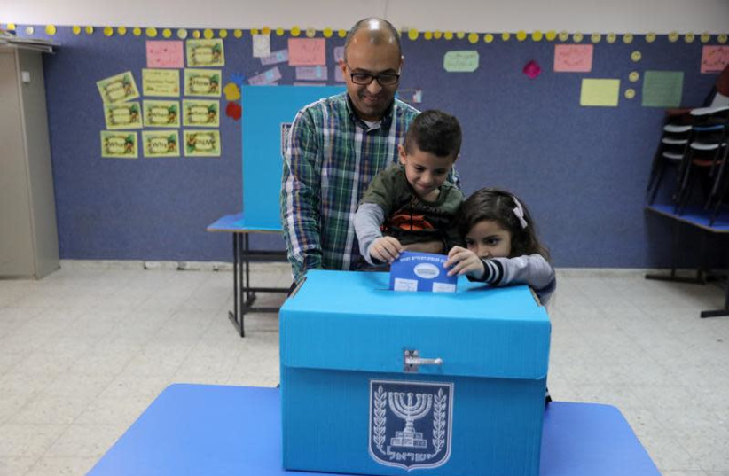 An Israeli-Arab father casts a ballot together with his children, as Israelis vote in a parliamentary election, at a polling station in Umm al-Fahm, Israel April 9, 2019 (photo credit: AMMAR AWAD / REUTERS)