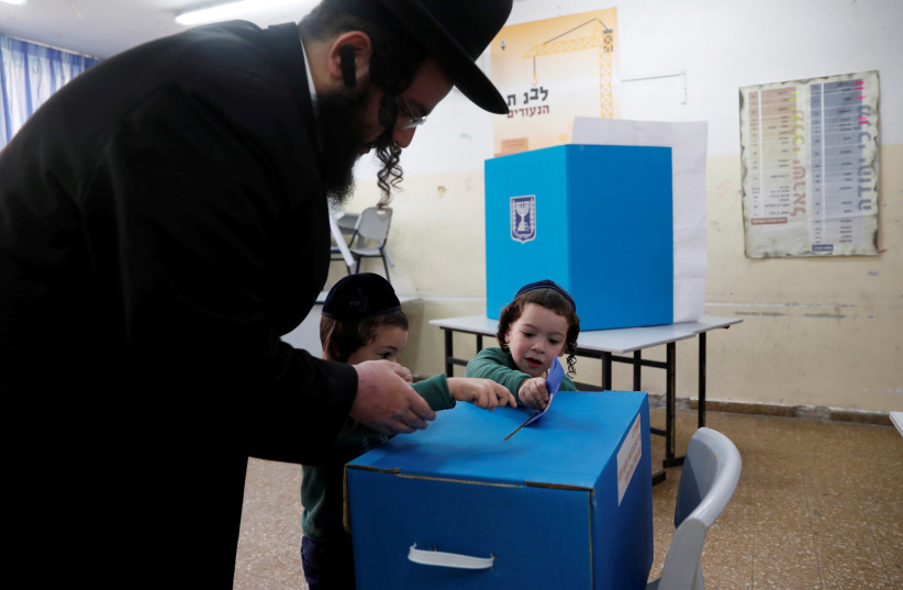 An ultra-Orthodox Jewish man helps kids cast his ballot at a polling station as Israelis vote in a parliamentary election, in Jerusalem April 9, 2019 (photo credit: RONEN ZVULUN/REUTERS)