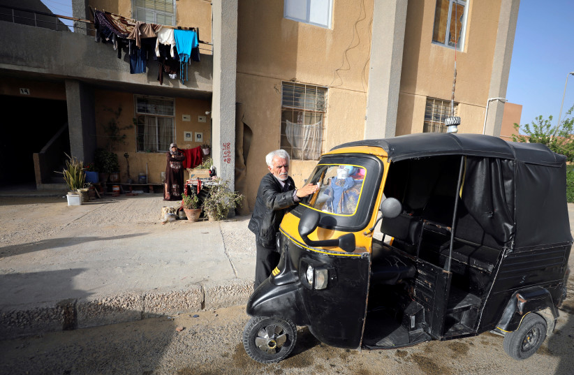 Syrian refugee Ahmad al-Khatib cleans his auto rickshaw as his wife Ilham Mohammad watches, outside their home in Cairo, Egypt April 8, 2019 (photo credit: MOHAMED ABD EL GHANY/REUTERS)