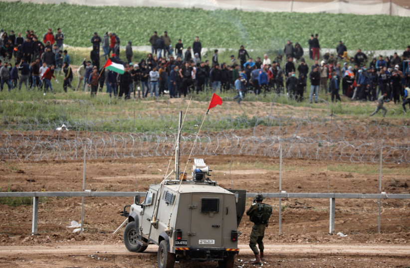 IDF troops face Palestinian protesters over the border fence between Israel and the Gaza Strip on March 30, a year after they began the 'Great March of Return' demonstrations (photo credit: AMIR COHEN/REUTERS)