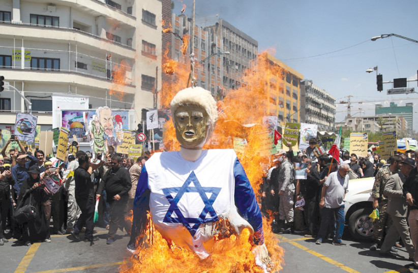 Iranian protesters burn an effigy in the likeness of US President Donald Trump dressed in an Israeli flag during a demonstration marking Jerusalem Day on June 8, 2018 (photo credit: REUTERS/TASNIM NEWS AGENCY)
