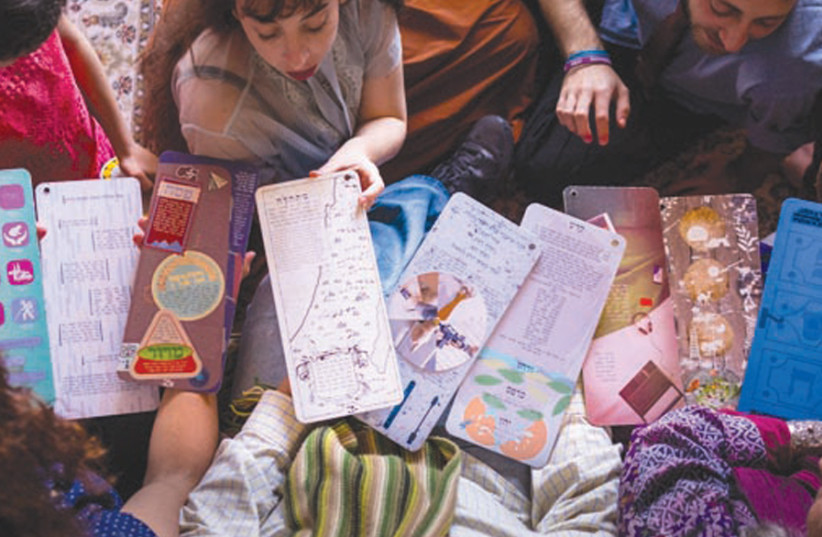 All members of the family enjoy the playful cards of the Unbound Haggadah (photo credit: Courtesy)