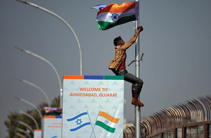 A MAN climbs a pole during Benjamin Netanyahu's visit to India in January 2018 (photo credit: REUTERS)