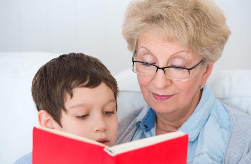 A bubbie reads to her grandchild (illustrative) (photo credit: INGIMAGE)