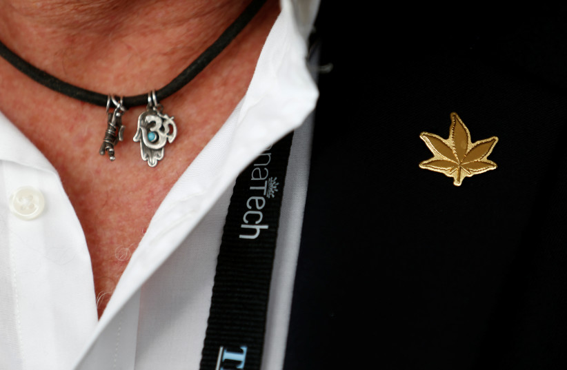 An attendee wears a golden pin in the shape of a cannabis leaf during Cannatech 2017, an annual global cannabis industry event, in Tel Aviv, Israel March 20, 2017 (photo credit: AMIR COHEN/REUTERS)