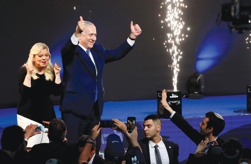 PRIME MINISTER Benjamin Netanyahu and his wife, Sara, celebrate at Likud Party headquarters in Tel Aviv late Tuesday night, April 9, 2020 (photo credit: RONEN ZVULUN/REUTERS)