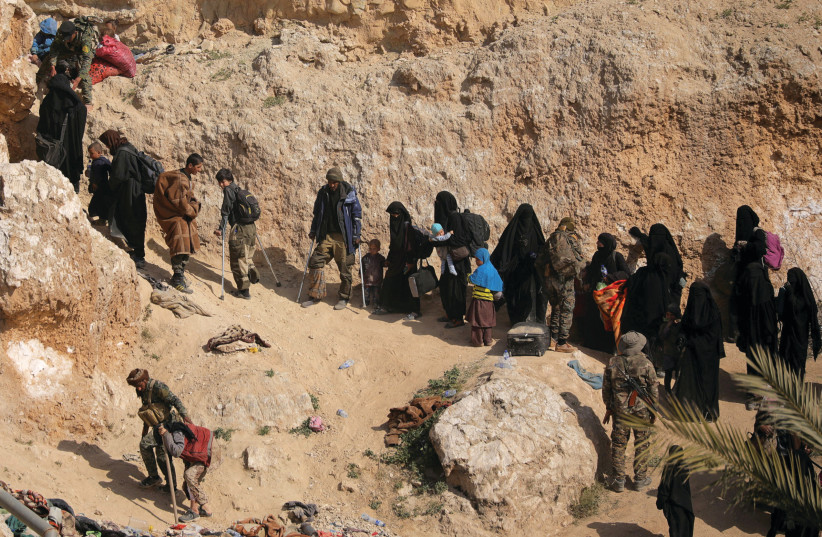 WOMEN AND their families surrender in the last ISIS-held area in Syria last month (photo credit: REUTERS)