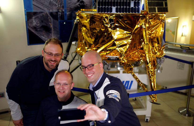 SpaceIL co-founders Kfir Damari (L), Yonatan Weintraub (C) and Yariv Bash (R) take a selfie in front of a model of the Beresheet spacecraft, near the control room, in Yahud, Israel, April 11, 2019 (photo credit: AMIR COHEN/REUTERS)