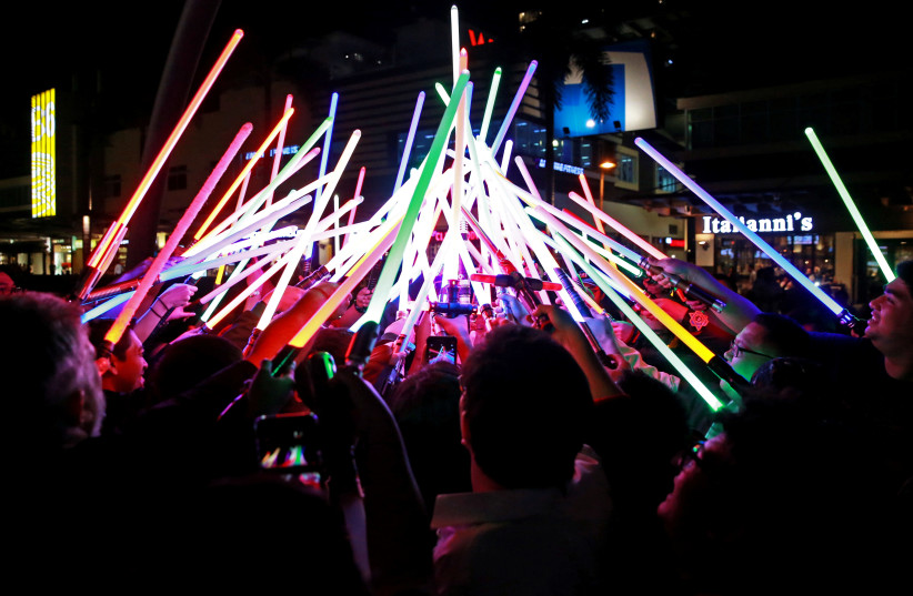 Star Wars enthusiasts huddle with their lightsabers after participating in Earth Hour at Taguig City, Philippines, March 30, 2019 (photo credit: REUTERS/ELOISA LOPEZ)