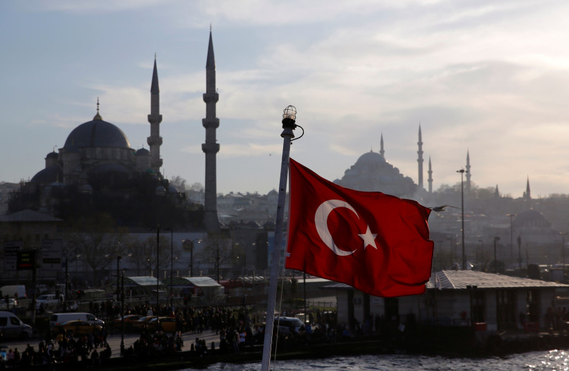 A Turkish flag, with the New and the Suleymaniye mosques in the background, flies on a passenger ferry in Istanbul, Turkey, April 11, 2019. (photo credit: MURAD SEZER/REUTERS)