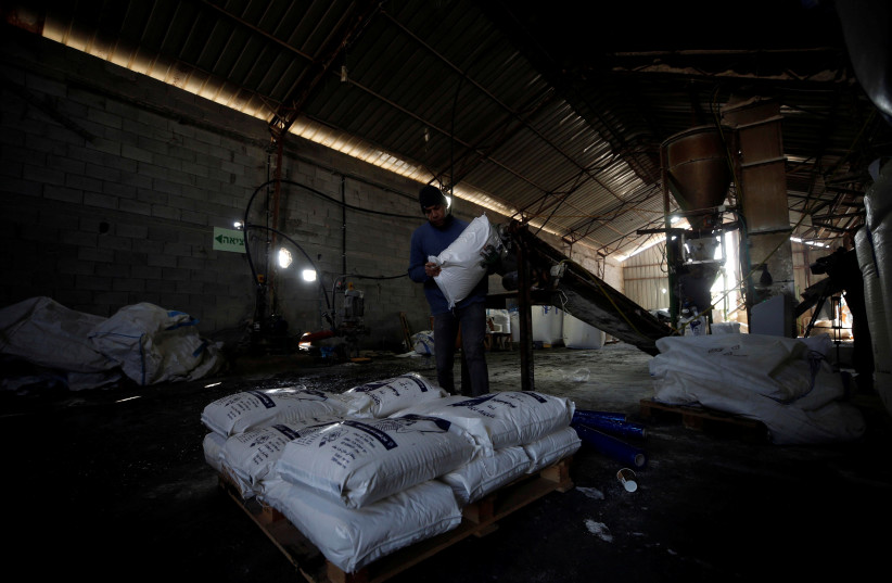 Palestinian worker carries a bag of salt at a factory near Jericho, West Bank, 2018.  (photo credit: REUTERS/MOHAMAD TOROKMAN)
