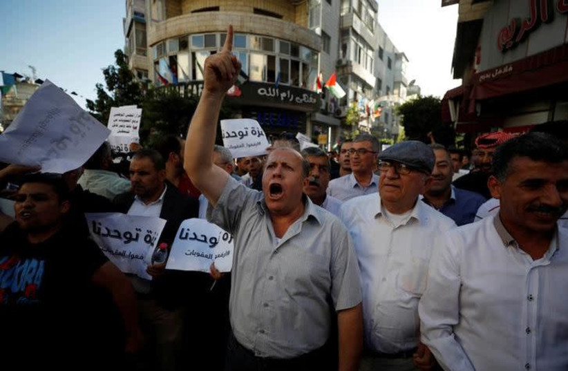 Palestinians take part in a protest calling on President Mahmoud Abbas to lift the sanctions on Gaza Strip, in Ramallah, in the occupied West Bank, June 23, 2018.  (photo credit: REUTERS/MOHAMAD TOROKMAN)
