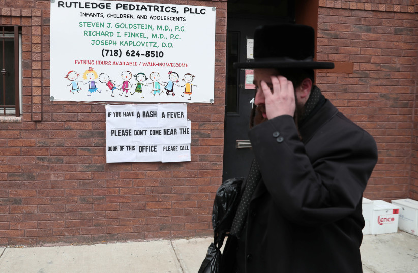 A sign warning people of measles in the ultra-Orthodox Jewish community of Williamsburg, two days after New York City Mayor Bill de Blasio declared a public health emergency in parts of Brooklyn in response to a measles outbreak, is seen in New York, U.S., April 11, 2019 (photo credit: SHANNON STAPLETON / REUTERS)