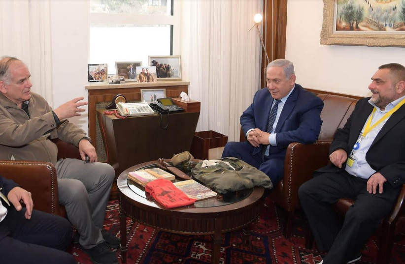 Ido Netanyahu [second from left] and Prime Minister Benjamin Netanyahu [second from right] accept personal items that used to belong to their late brother Yonatan Netanyahu from a former soldier of the late Netanyahu Yosef Shemesh [right]. (photo credit: AMOS BEN-GERSHOM/GPO)