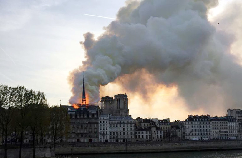 Smoke billows from the Notre Dame Cathedral after a fire broke out, in Paris, France, April 15, 2019 (photo credit: REUTERS/JULIE CARRIAT)