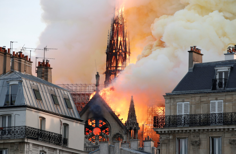 Smoke billows as fire engulfs the spire of Notre Dame Cathedral in Paris, France April 15, 2019 (photo credit: REUTERS/BENOIT TESSIER)