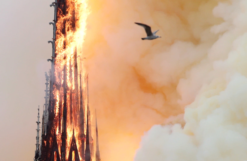 Smoke billows as fire engulfs the spire of Notre Dame Cathedral in Paris, France April 15, 2019.  (photo credit: BENOIT TESSIER /REUTERS)