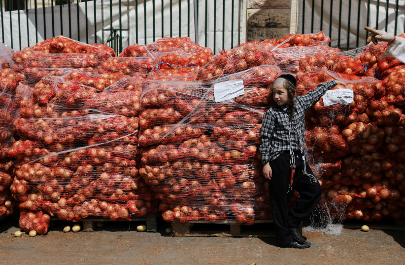 An ultra-Orthodox Jewish boy leans against sacks of onions at a food distribution center providing food products for families ahead of the upcoming Jewish holiday of Passover in Jerusalem's Mea Shearim neighbourhood, April 16, 2019 (photo credit: AMMAR AWAD / REUTERS)