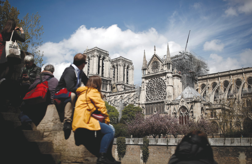 PEOPLE GAZE at the Notre-Dame Cathedral in Paris two days after a massive fire devastated large parts of the gothic structure (photo credit: REUTERS/BENOIT TESSIER)