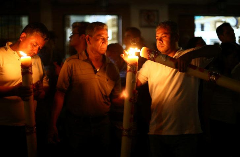 People hold candles (photo credit: REUTERS/EDGARD GARRIDO)