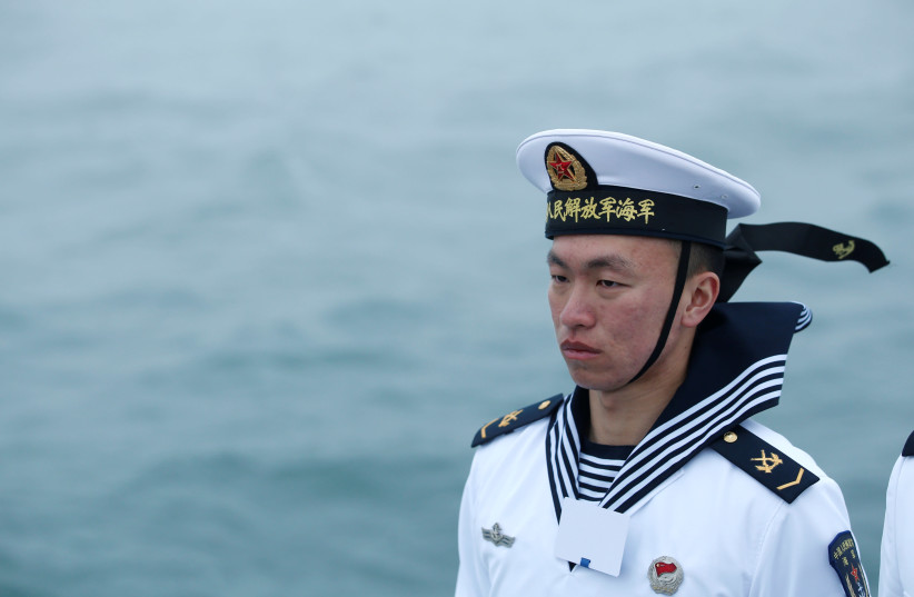 A Chinese navy personnel stands guard during a naval parade off the eastern port city of Qingdao to mark the 70th anniversary of the founding of Chinese People's Liberation Army Navy, China, April 23, 2019.  (photo credit: JASON LEE / REUTERS)