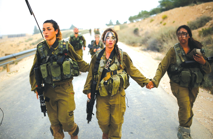 Women in an IDF combat unit help one of their fellow fighters during a training exercise (photo credit: REUTERS)