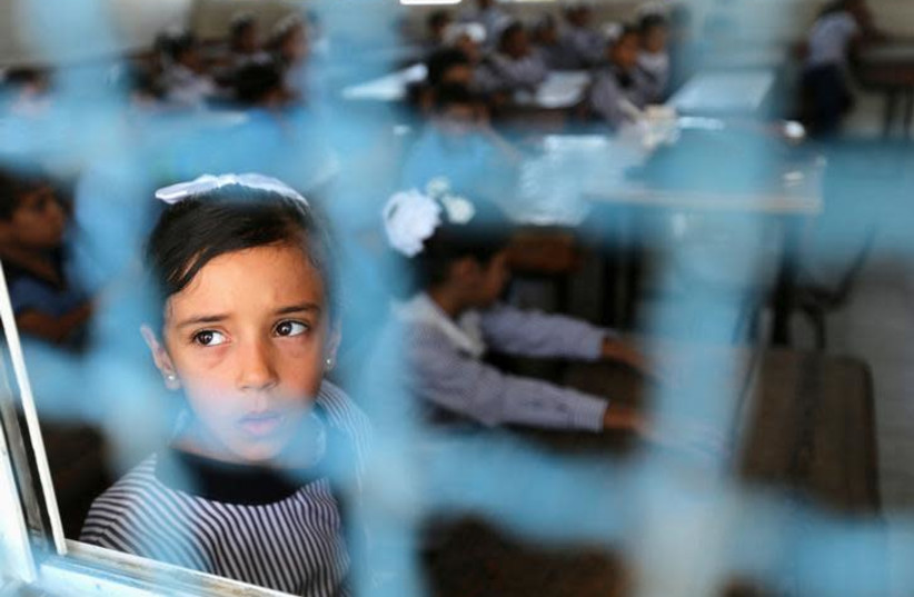 A Palestinian girl looks out of a classroom window as she attends a lesson on the first day of a new school year, at a United Nations-run school in Khan Young in the southern Gaza Strip (photo credit: REUTERS/IBRAHEEM ABU MUSTAFA)
