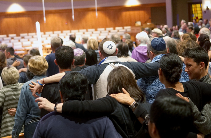 Mourners participate in a vigil for the victims of the Chabad of Poway Synagogue shooting at the Rancho Bernardo Community Presbyterian Church on April 27, 2019 in Poway, California (photo credit: SANDY HUFFAKER / AFP)