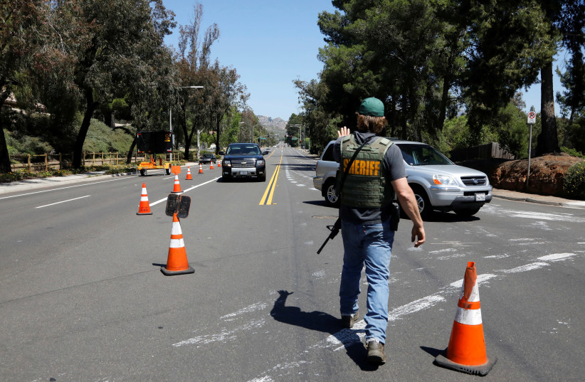 A San Diego County Sheriff's Deputy secures the scene of a shooting incident at the Congregation Chabad synagogue in Poway, north of San Diego, California, U.S. April 27, 2019 (photo credit: JOHN GASTALDO/REUTERS)