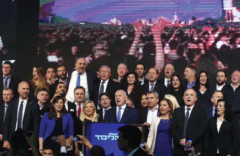 Prime Minister Benjamin Netanyahu and his wife, Sara, are joined by Likud members in the singing of 'Hatikvah' after celebrating their victory on April 10 (photo credit: MARC ISRAEL SELLEM)