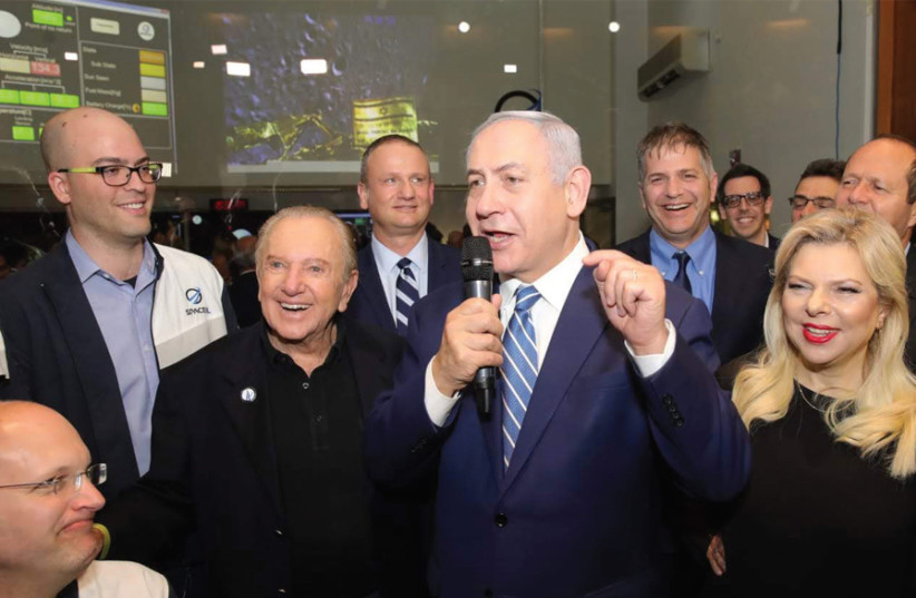 Prime Minister Benjamin Netanyahu (center) is flanked by (from left) two of the SpaceIL co-founders Yariv Bash, Yonatan Winetraub, SpaceIL President Morris Kahn and IAI Chairman Harel Locker, and his wife Sara (from the right) (photo credit: SPACEIL IAI)