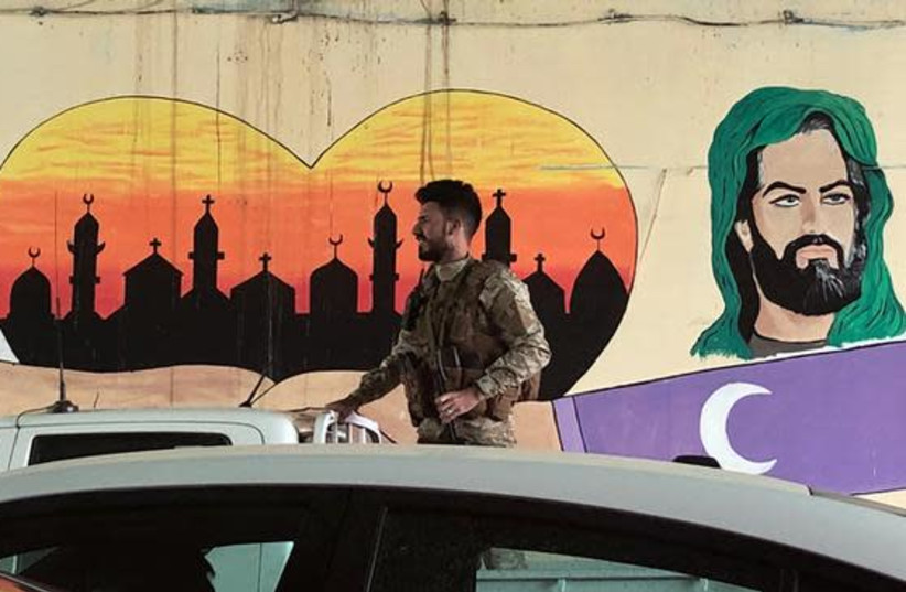 An Iraqi Popular Mobilisation Forces (PMU) member rides on the back of a pickup truck past a Shi'ite mural in Baghdad, Iraq (photo credit: REUTERS/MARIUS BOSCH)