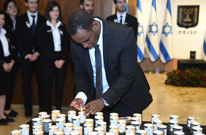 "Freshman Knesset member Gadi Yevarkan lights a candle in memory of the victims of the Holocaust at the Knesset's annual ""Every Person Has a Name"" ceremony, May 2 2019. (photo credit: KNESSET SPOKESMAN'S OFFICE)"